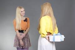 Молодая женщина давая настоящий момент к ее другу над серым цветом Стоковые Изображения RF