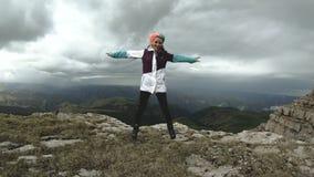 Молодая женщина девушки танцует на краю скалы плато имея привлекательное цветков гор природы потехи красивое сток-видео