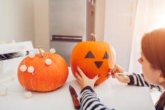 Молодая женщина делая Джек-o-фонарик на хеллоуин на кухне Рисуя глаза, нос и рот с ручкой на тыкве стоковая фотография