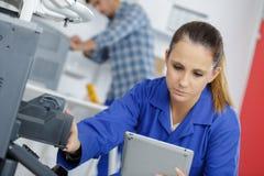 Молодая женщина делая обслуживание принтера Стоковое Фото