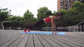 Молодая женщина делая планку тренировки outdoors видеоматериал