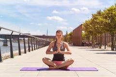 Молодая женщина делая положение лотоса йоги в городе рекой, Стоковые Изображения RF