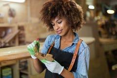 Молодая женщина делая работу по дереву в мастерской Стоковые Изображения RF