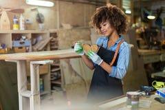 Молодая женщина делая работу по дереву в мастерской Стоковое фото RF