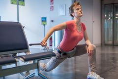 Молодая женщина делая тренировки в зале авиапорта пока ждущ fo Стоковые Фотографии RF