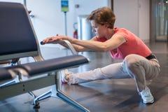 Молодая женщина делая тренировки в зале авиапорта пока ждущ fo Стоковая Фотография RF