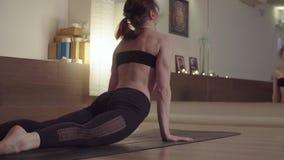 Молодая женщина делая тренировки йоги - передний загиб видеоматериал