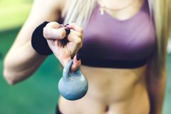 Молодая женщина делая тренировки с гантелями в СПОРТЗАЛЕ Владение пальца Стоковое Изображение RF
