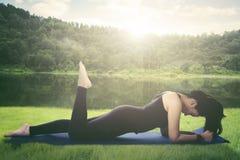 Молодая женщина делая тренировку планки в парке Стоковое Изображение RF