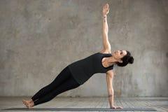 Молодая женщина делая тренировку Vasisthasana Стоковое фото RF