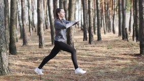Молодая женщина делая фитнес работает outdoors Подходящая девушка делая выпады в парке сток-видео