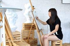 Молодая женщина делая эскиз к на мольберте стоковые фото