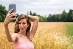 Молодая женщина делая selfies с ее мобильным телефоном снаружи стоковая фотография rf