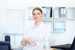 Молодая женщина дела сидя на столе в офисе Стоковое фото RF