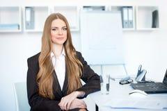 Молодая женщина дела сидя на столе в офисе Стоковая Фотография RF