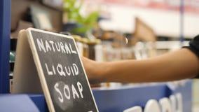 Молодая женщина держа бутылку геля шампуня жидкостного мыла в магазине супермаркета косметик 4K видеоматериал