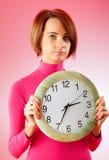 Молодая женщина держа вокруг часов Стоковая Фотография