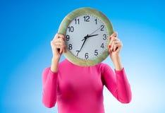 Молодая женщина держа вокруг часов Стоковое Фото