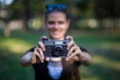 Молодая женщина держа в камере рук старой винтажной стоковые фото