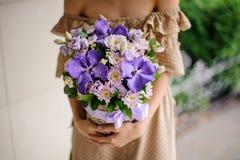 Молодая женщина держа корзину фиолетовых цветков Стоковое Изображение RF