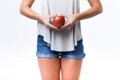 Молодая женщина держа красное яблоко над белой предпосылкой Стоковое Фото