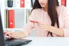Молодая женщина держа кредитную карточку в руке и входя в код защиты используя клавиатуру компьтер-книжки принципиальная схема Ко стоковое фото