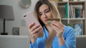 Молодая женщина держа кредитную карточку и используя смартфон Онлайн ходя по магазинам концепция, легкая оплата используя цифрово видеоматериал