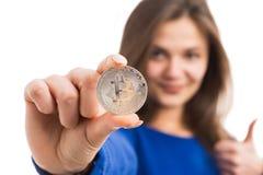 Молодая женщина держа серебряное bitcoin стоковое фото