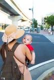 Молодая женщина держа сына рядом с улицей стоковое фото