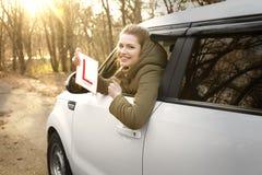 Молодая женщина держа wh знака водителя учащийся стоковое изображение rf