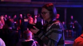 Молодая женщина держит камеру и принимает фото представления на этапе на фестиваль видеоматериал