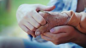 Молодая женщина держит пожилую руку ` s дамы Внучка держит руку его baushka в его руках стоковая фотография rf
