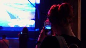 Молодая женщина держит смартфон в руках сидя рядом с этапом на зале фестиваля сток-видео