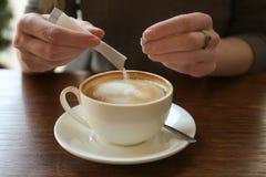 Молодая женщина добавляя сахар к очень вкусному кофе стоковая фотография rf