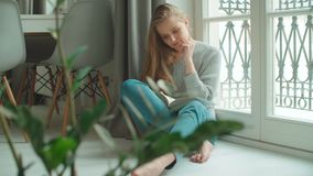 Молодая женщина дома сидя около книги чтения окна и ослабляя сток-видео
