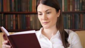 Молодая женщина дома читая физическую книгу печати Концепция старого традиционного классического бумажного чтения видеоматериал