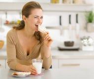 Молодая женщина есть заедки в самомоднейшей кухне стоковые изображения
