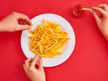 Молодая женщина есть картошку французских фраев с кетчуп в ресторане Стоковое Фото
