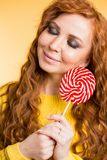 Молодая женщина есть леденец на палочке конфеты стоковое изображение rf