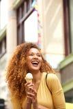 Молодая женщина есть мороженое в городе стоковая фотография