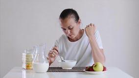 Молодая женщина ест корнфлексы с молоком на завтрак с аппетитом видеоматериал