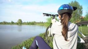 Молодая женщина ехать велосипед через парк на предпосылке озера или реки сток-видео