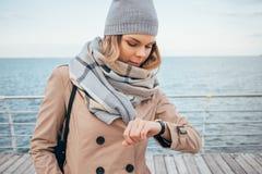 Молодая женщина ждет встречу и контрольное время на наручных часах стоковые изображения