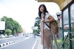 Молодая женщина ждет на автобусной остановке стоковые фото