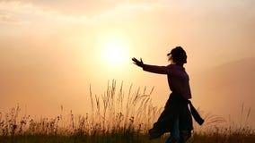 Молодая женщина закручивает на восход солнца в горах
