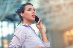 Молодая женщина занятая с вызывать, беседующ на портрете взгляда со стороны сотового телефона стоковое фото