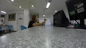Молодая женщина заполняя вверх по форме банка на столе для того чтобы примениться для учета сток-видео
