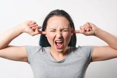Молодая женщина заткнула ее уши с ее пальцами стоковые фото