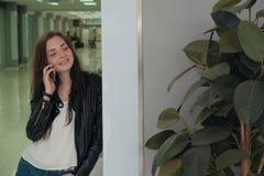 Молодая женщина звонит на идет говорить счастливо полагаясь сторону со стеной стоковое изображение