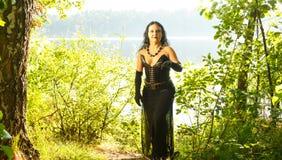 Молодая женщина знахарка в черноте озером halloween стоковая фотография rf